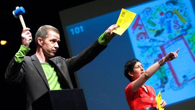 Eine Bühne, auf der ein Moderator (Urs Wehrli) und eine Moderatorin (Monika Schaerer) eine Auktion leiten.