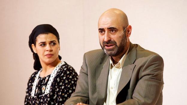 Ein Mann und eine Frau auf der Bühne. Die Frau sitzt hinter ihm und schaut ihn an. Er starrt gerade aus mit einem besorgten Blick.