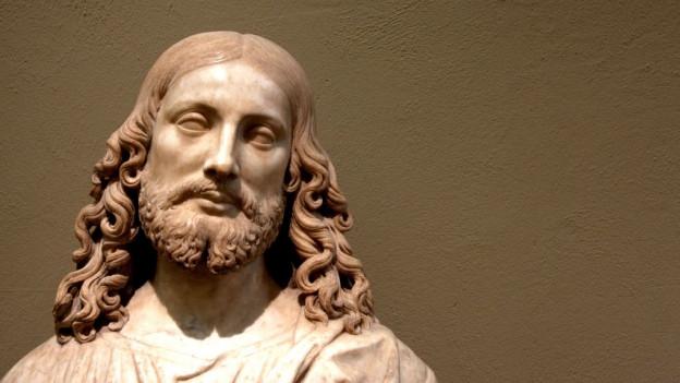 Metallfigur von Jesus am Kreuz. Aufgrund der Beleuchtung sind nur die Umrisse der Figur ersichtlich.