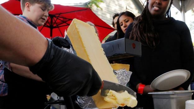 Raclette wird zubereitet, der geschmolzene Käse wird abgeschabt.