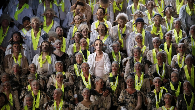 Menschen sind wie bei einem Chor auf einer Treppe hintereinander augestellt. Sie sind wie Monster verkleidet und geschminkt.