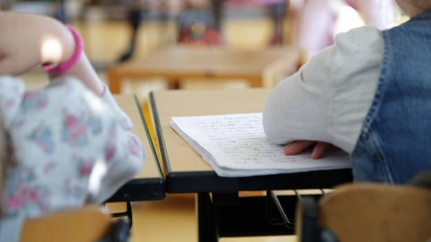 Nahaufnahme mit Rückensicht von Schulkkindern im Unterricht