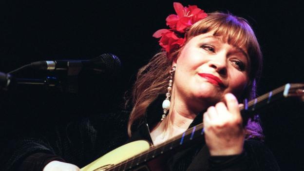 Dodo Hug mit Gitarre und Mikrofon auf der Bühne