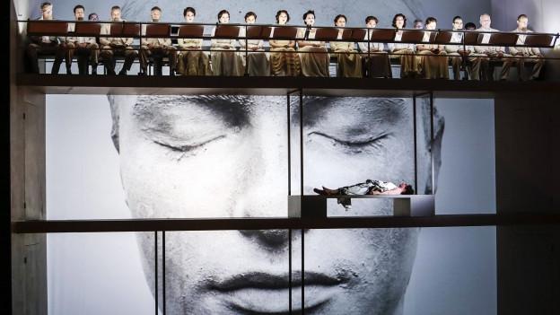 Bühnenbild der Oper: Auf einem Gerüst sitzen die Sänger, weiter unten liegt eine Person auf einer Bank, im Hintergrund ist ein Bild eines weiss angemalten Gesichtes auf eine Leinwand projiziert.