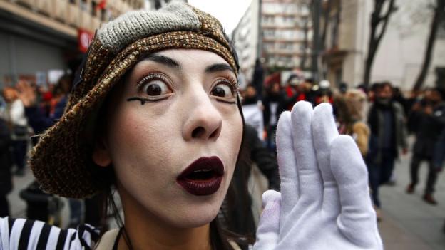 Eine weiss geschminkte Person macht Pantomimen.