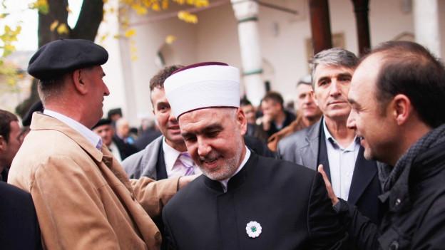 Der bosnische Grossmufti ist in einer Menschenmenge und wird von verschiedenen Seiten beglückwünscht.