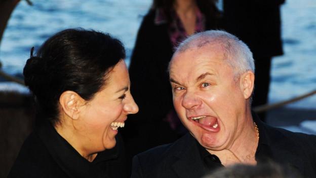 Bild von Damien Hirst mit einer Frau auf einer Party. Er schneidet eine Grimasse.