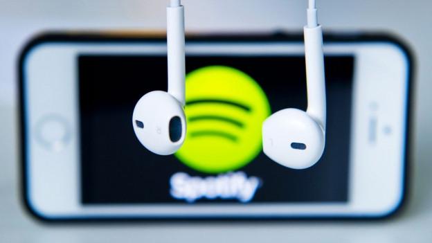 Kopfhörer im Vordergrund, im Hintergrund ein Handy, auf dessen Bildschirm das Emblem des Musikstreamingdienstes «Spotify» zu sehen ist.