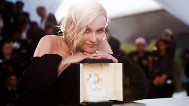 Foto von der Schauspielerin Diane Kruger mit ihrem Preis, den sie als Auszeichung zur besten Schauspielerin bekommen hat.