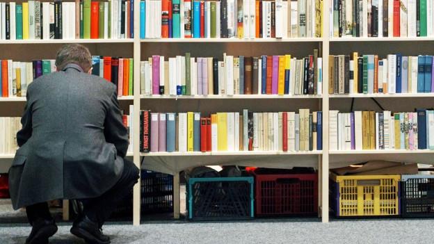 Ein Mann schaut sich Bücher in einem Bücherregal an