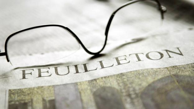 Foto einer Zeitung mit der Auschrift «Feuilleton» und darauf eine Brille.