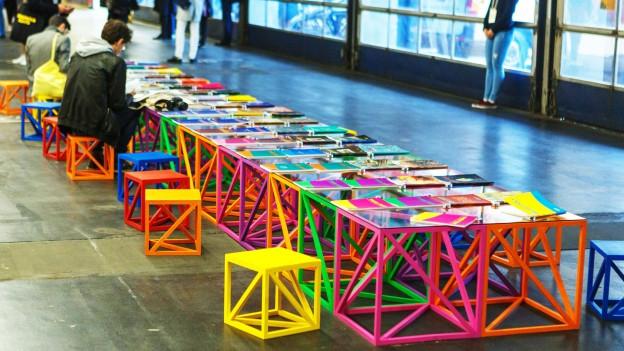 In einem Ausstellungsraum stehen kleine farbige Stühle und Tische mit Prospekten drauf.