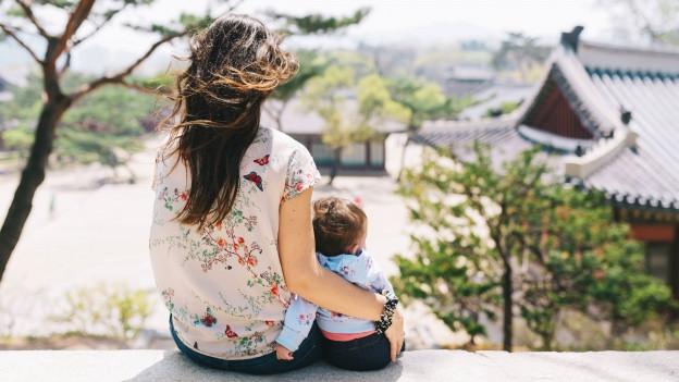 Eine Mutter und eine Baby sind in Rückenansicht zu sehen, während sie gemeinsam auf einer Mauer sitzen.