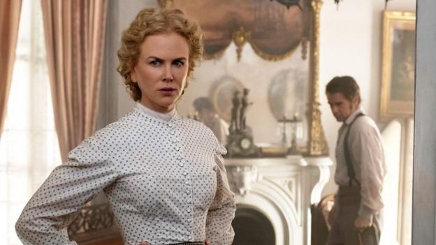 Eine Frau in einem Kleid aus dem Viktorianischen Zeitalter steht in einem historisch wirkenden Raum, im Hintergrunf ein Mann.