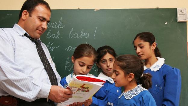 Ein Leherer erklärt drei Schülerinnen in Uniform etwas aus einem Buch.
