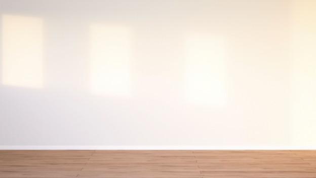 Ein leerer, weisser Raum mit Holzparkett