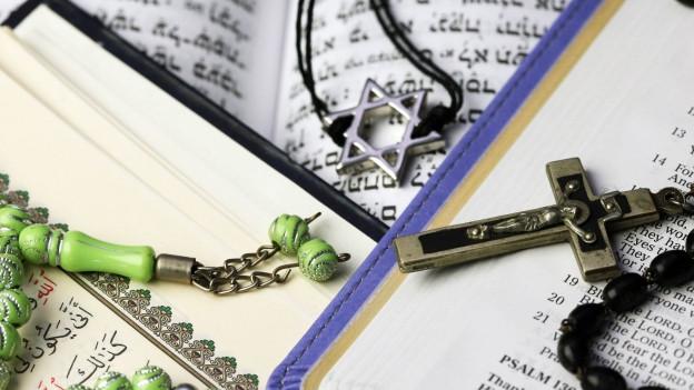 Die Bibel und der Koran nebeneinander, darauf die Symbole für das Christentum, das Judentum und den Islam