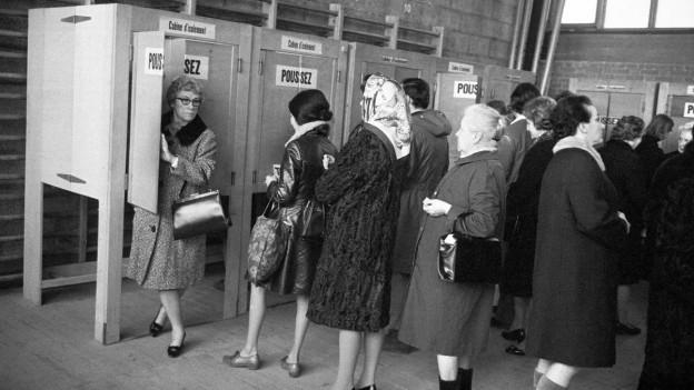 Schwarzweiss Foto von Frauen, die vor der Urne anstehen, um ihren Stimmzettel einzuwerfen.