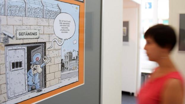 Eine Frau steht vor einer Karikatur in einem Museum.