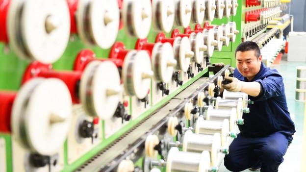 Symbolbild: Ein Arbeiter in China inspiziert Einstellungen einer Maschine.