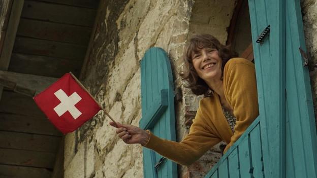 Jane Birkin iwinkt mit einer Schweizer Fahne aus einem kleinen Haus.