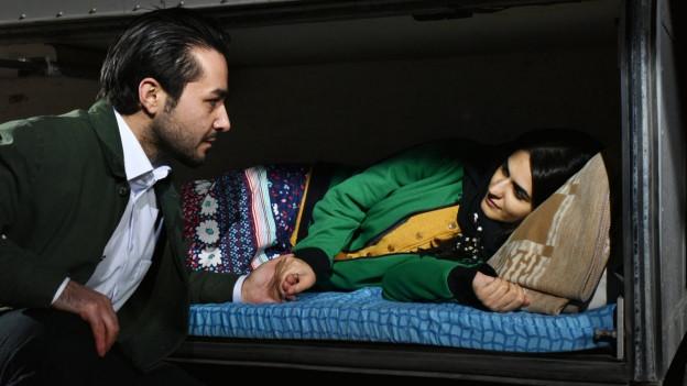 Eine Frau liegt auf einer Matratze, ein Mann hält ihre Hand.