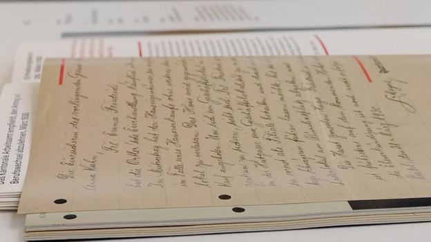 Altes Papier mit Handschrift auf einem Ausstellungstisch.