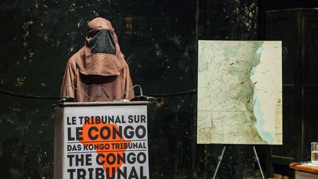 """Eine vermumte Person steht hinter einem Podest mit der Aufschrift """"Le Tribunal sur le Congo"""""""