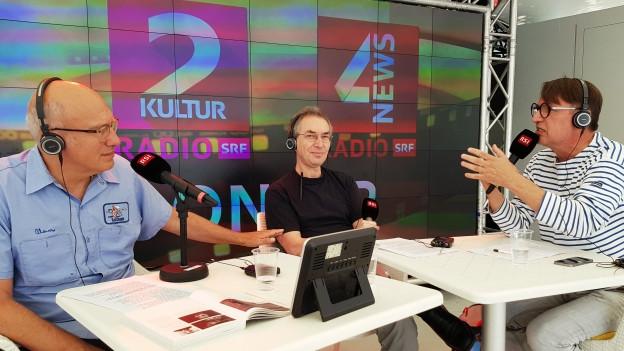 Drei Männer sitzen an einem Tische vor Radiomikrofonen