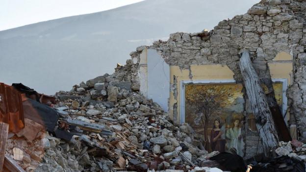 Ein Fresco liegt in Schutt und Trümmern eines Gebäudes begraben