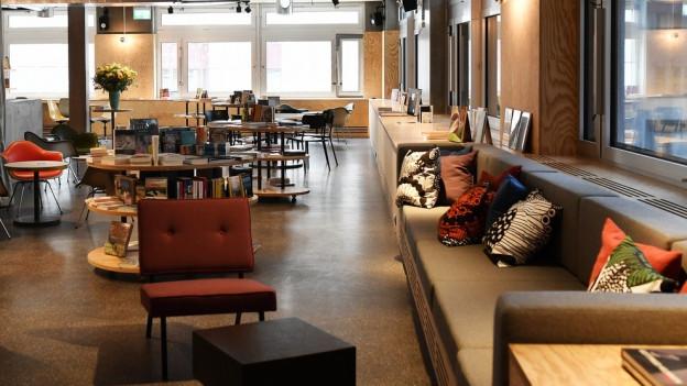 Raum mit Büchern und Sesseln.