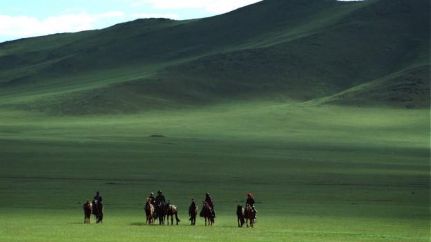 Eine Gruppe Nomaden auf Pferden in einer grünen Berglandschaft