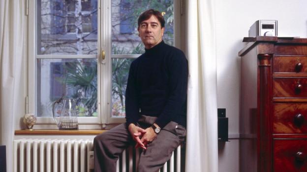 Der Schriftsteller Alain Claude Sulzer sitzt am Fenster einer Wohnstube