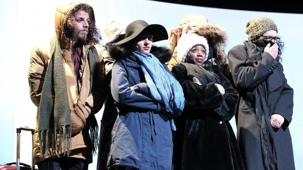 Sechs Schauspieler des Exil Ensembles stehen in dicken Wintermänteln auf der Bühne