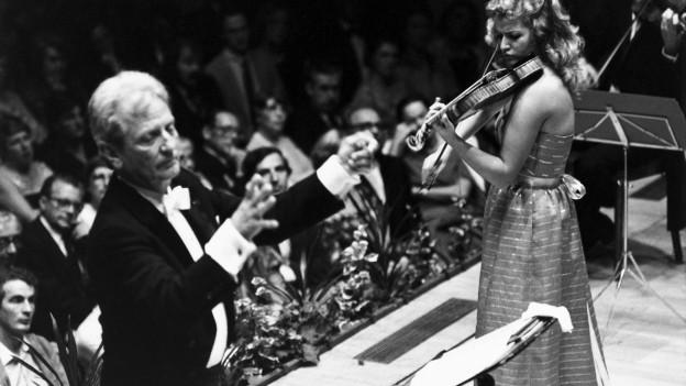Der Dirigent Rudolf Baumgartner mit der Violinistin Anne-Sophie Mutter auf einer Bühne