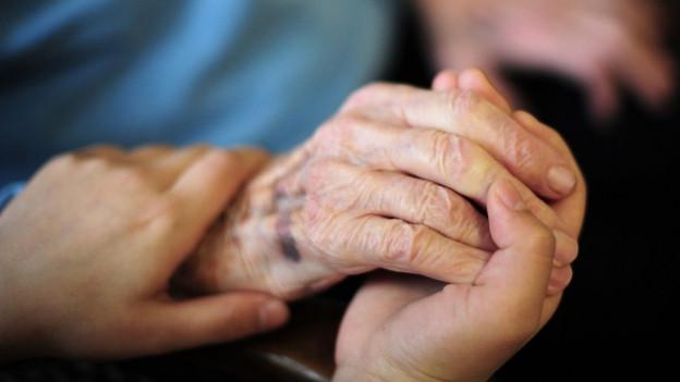 Eine junge Hand hält eine alte Hand