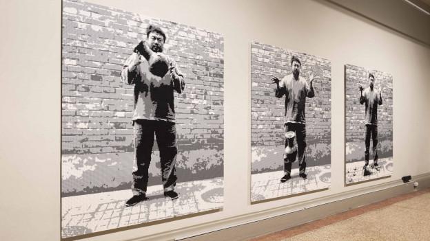 Drei lebensgrosse Ganzkörperfotografien des Künstlers hängen an der Wand eines Museums