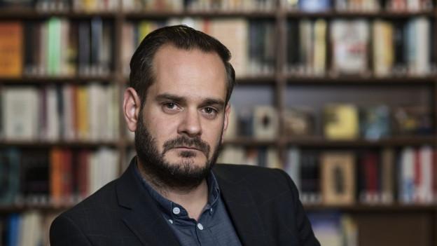 Portrait des Autors vor einer Bibliothek