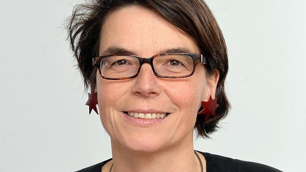 Eine Frau mit kurzen Haaren und Sternohringen.