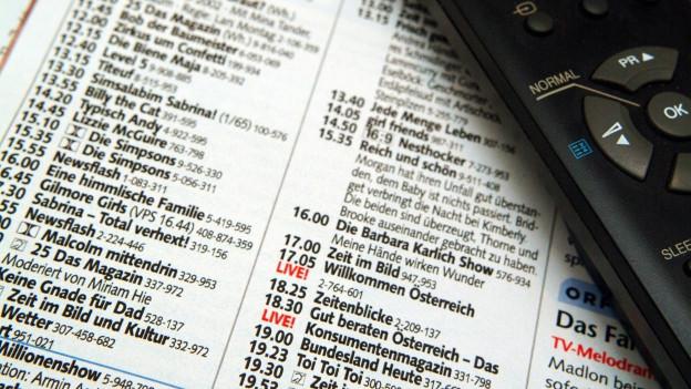 Blick in eine Fernsehzeitung mit Fernbedienung