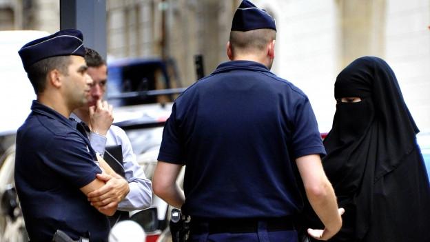Eine Burkaträgerin mit einem Polizeibeamten an einer Strassenecke