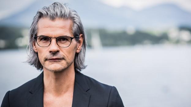 Ein Mann mittleren Alters, graue Haare, schwarze Brille, schwarz gekleidet