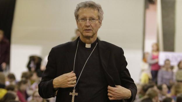 Ein Pfarrer mittleren Alters mit Kruzifix-Kette und ernstem Blick