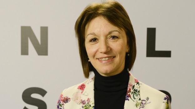 Eine Frau in geblümten Jacket steht vor dem Logo der Bienal Sur