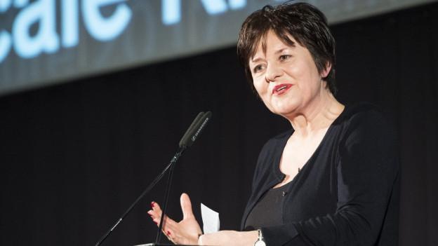 Eine Frau mit kurzen dunklen Haaren und dunkler Kleidung spricht an einem Rednerpult