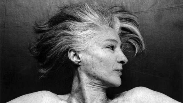Fotographie einer Frau: Sie liegt am Boden und schaut zur Seite