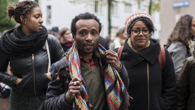 Zwei Frauen und ein Mann dunkler Hautfarbe
