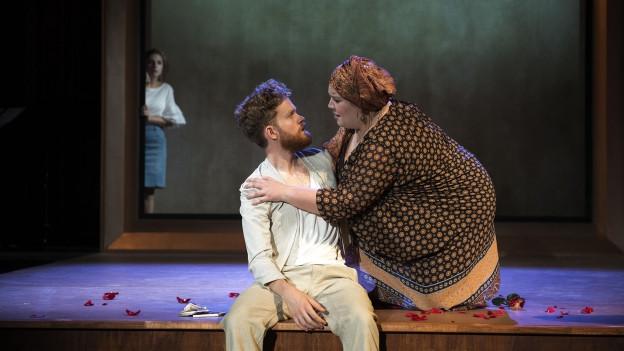 Ein Mann und eine Frau sitzen einander zugewandt auf einer Bühne, im Hintergrund eine dritte Frau