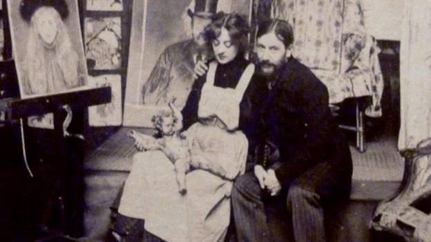 Eine alte Schwarzweissfotographie zeigt einen Mann und eine Frau vor Staffeleien mit Bildern