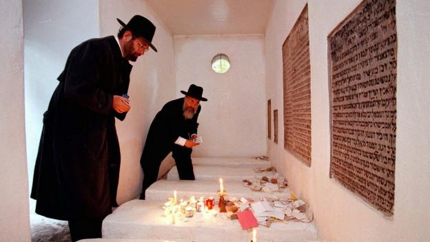 Zwei jüdische Geistliche in einer hellen Gruft mit Kerzen und Gebetsteppichen
